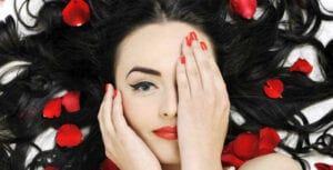 Beautiful Raven Haired Woman with Red Flower Petals - VOLUPTE - Crop - Blog - Featured