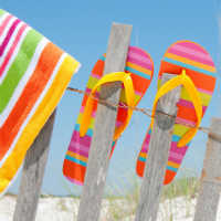 Striped Flip Flops and Towel on Fence at Beach - CC - 200X200